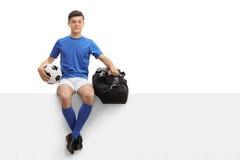 Jugador de fútbol adolescente con fútbol y bolso que se sienta en el panel Imagenes de archivo