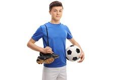 Jugador de fútbol adolescente con fútbol y pares de zapatos del fútbol Imágenes de archivo libres de regalías