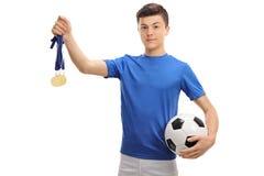 Jugador de fútbol adolescente con medallas de oro y un fútbol Fotos de archivo