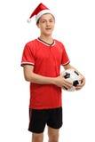 Jugador de fútbol adolescente con un sombrero de la Navidad Foto de archivo