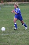 Jugador de fútbol adolescente de la muchacha que persigue la bola Foto de archivo libre de regalías