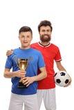 Jugador de fútbol adolescente que celebra un trofeo de oro con su padre Imágenes de archivo libres de regalías