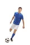 Jugador de fútbol adolescente que golpea un fútbol con el pie Imagen de archivo libre de regalías