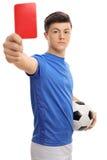 Jugador de fútbol adolescente que muestra una tarjeta roja Fotografía de archivo