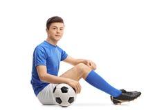 Jugador de fútbol adolescente que se sienta en el piso Fotos de archivo