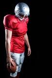 Jugador de fútbol americano con la bola que mira abajo Imagenes de archivo