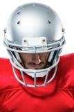 Jugador de fútbol americano confiado en el jersey rojo que mira abajo Imagen de archivo