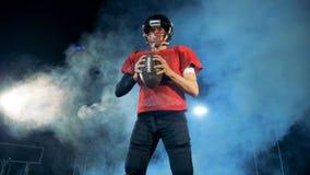 Jugador de fútbol americano El jugador de fútbol americano se coloca con una bola en estadio nublado oscuro almacen de video