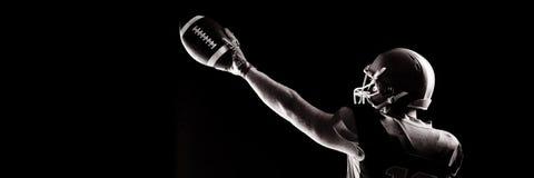Jugador de fútbol americano en el casco que sostiene la bola de rugbi fotos de archivo libres de regalías