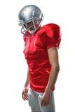 Jugador de fútbol americano en el jersey rojo que mira abajo Fotos de archivo