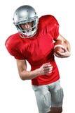 Jugador de fútbol americano en el jersey rojo que mira abajo mientras que sostiene la bola Fotografía de archivo