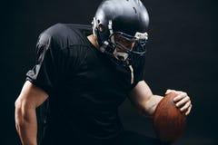 Jugador de fútbol americano en sportwear negro con una bola en fondo negro imagen de archivo