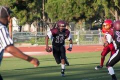 Jugador de fútbol americano que corre con la bola Imagenes de archivo