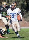 Jugador de fútbol americano que corre con la bola durante un juego Fotografía de archivo
