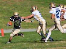 Jugador de fútbol americano que corre con la bola durante un juego Foto de archivo libre de regalías