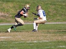 Jugador de fútbol americano que corre con la bola durante un juego Foto de archivo