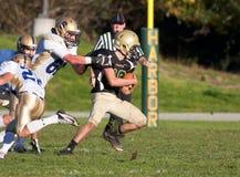 Jugador de fútbol americano que corre con la bola durante un juego Imagen de archivo