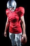 Jugador de fútbol americano que mira abajo mientras que se coloca Fotografía de archivo libre de regalías