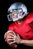 Jugador de fútbol americano resuelto que parece ausente mientras que sostiene la bola fotos de archivo