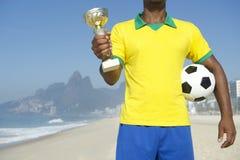 Jugador de fútbol brasileño del campeón que celebra el trofeo y el fútbol imagenes de archivo