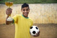 Jugador de fútbol brasileño joven del fútbol que celebra el trofeo Imagen de archivo libre de regalías