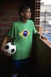 Jugador de fútbol brasileño joven serio que mira hacia fuera la ventana de Favela Foto de archivo