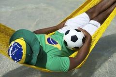Jugador de fútbol brasileño que se relaja en hamaca de la playa Fotos de archivo
