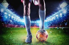 Jugador de fútbol con el soccerball en el fuego en el estadio durante el partido foto de archivo