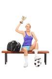 Jugador de fútbol de sexo femenino que celebra un trofeo Fotos de archivo libres de regalías