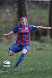 Jugador de fútbol de sexo femenino que golpea la bola con el pie Imagen de archivo libre de regalías