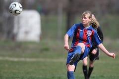 Jugador de fútbol de sexo femenino que golpea la bola con el pie Fotos de archivo libres de regalías