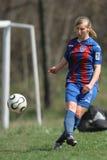 Jugador de fútbol de sexo femenino que golpea la bola con el pie Fotografía de archivo libre de regalías