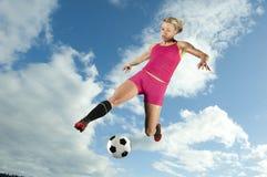 Jugador de fútbol de sexo femenino que golpea una bola con el pie Fotos de archivo