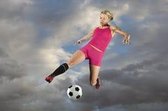 Jugador de fútbol de sexo femenino que golpea una bola con el pie Fotos de archivo libres de regalías