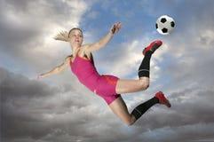 Jugador de fútbol de sexo femenino que golpea una bola con el pie Imagen de archivo