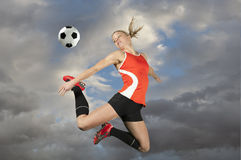 Jugador de fútbol de sexo femenino que golpea una bola con el pie Fotografía de archivo libre de regalías