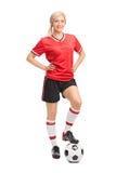 Jugador de fútbol de sexo femenino que presenta en el fondo blanco Fotos de archivo libres de regalías