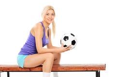 Jugador de fútbol de sexo femenino que se sienta en un banco Imagen de archivo libre de regalías