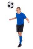Jugador de fútbol en el azul que golpea la bola con el pie por la cabeza aislada en blanco Imagen de archivo
