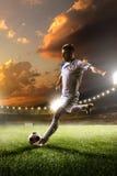 Jugador de fútbol en la acción en fondo del estadio de la puesta del sol Fotografía de archivo libre de regalías