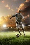 Jugador de fútbol en la acción en fondo del estadio de la puesta del sol Imagen de archivo