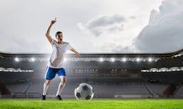 Jugador de fútbol en la arena de deporte Técnicas mixtas Foto de archivo libre de regalías