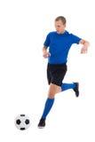 Jugador de fútbol en la bola de cuero de retroceso con el pie azul aislada en blanco Imagen de archivo