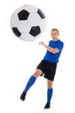 Jugador de fútbol en la bola de retroceso con el pie azul aislada en el fondo blanco Foto de archivo