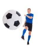 Jugador de fútbol joven en la bola de retroceso con el pie azul aislada en el backg blanco Fotografía de archivo
