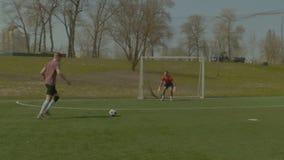 Jugador de fútbol joven que toma un tiro en meta almacen de metraje de vídeo