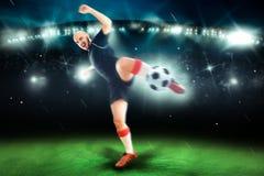 Jugador de fútbol profesional en el lanzamiento del juego la bola Foto de archivo libre de regalías