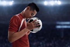 Jugador de fútbol que celebra el balón de fútbol Imágenes de archivo libres de regalías