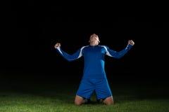 Jugador de fútbol que celebra a Victory On Black Background Fotografía de archivo