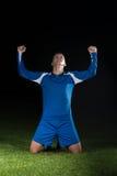 Jugador de fútbol que celebra a Victory On Black Background Foto de archivo libre de regalías